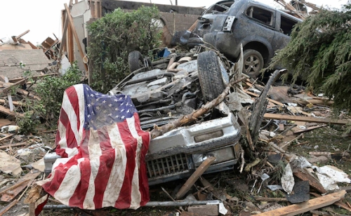 An American flag lies on top of an overturned car after a tornado struck Moore, Oklahoma