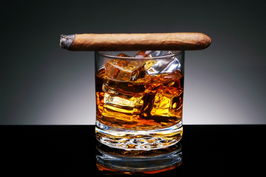 Lit Cigar resting on Glass of Whiskey and Ice cubes