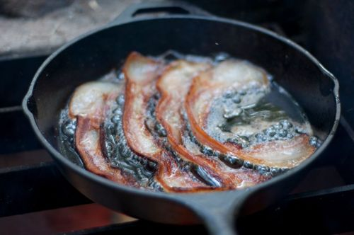 close-up-of-bacon-frying-in-pan-607830493-5ac197776bf06900371a10cb.jpg